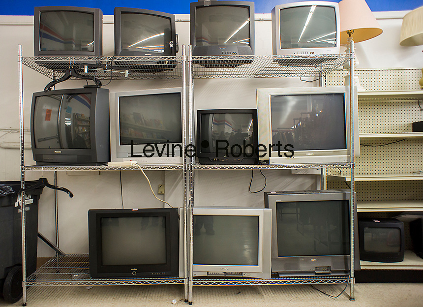Second-hand CRT analog television sets are seen lined up for sale in a thrift store in New York on Wednesday, November 13, 2013. Three years ago the country switched from analog to digital television with converter boxes being used on older sets such as these. (© Richard B. Levine)
