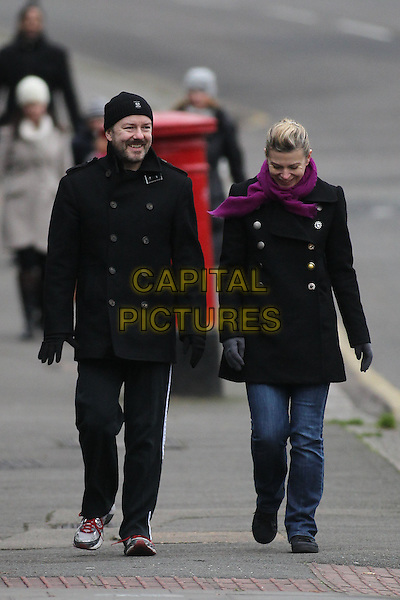 Ricky Gervais, Jane Fallon.walking in Primrose Hill, London, England 29th December 2011.full length couple jeans denim black coat jacket beanie hat purple pink scarf facial hair gloves .CAP/HIL.©John Hillcoat/Capital Pictures .