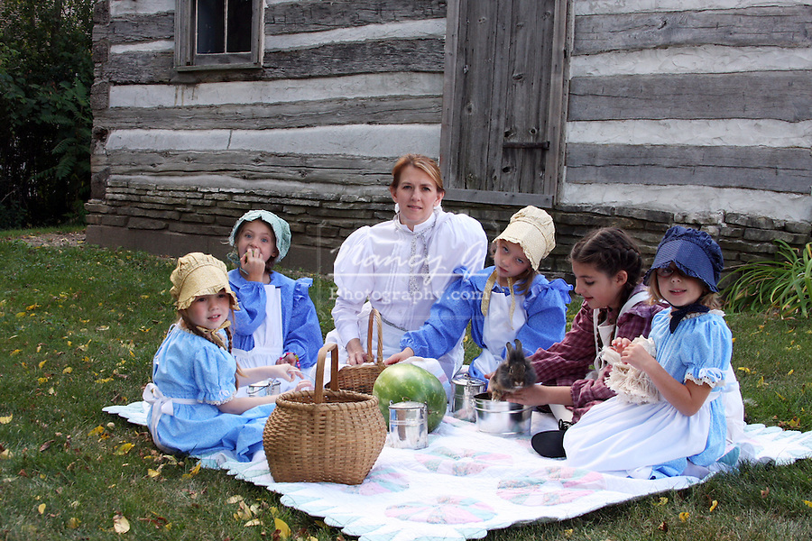 A young woman with children having a picnic in front of a log cabin