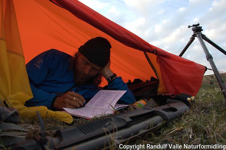 Mann ligger i telt og skriver dagbok. ---- Man in tent writing in a book.