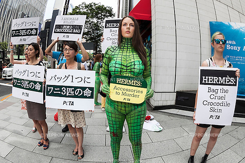 A body painted model with other members from PETA (the People For The Ethical Treatment of Animals organization) protest outside the luxury Hermes store in the upscale Ginza shopping district on July 30th, 2015 in Tokyo, Japan. PETA claims that Hermes bags and accessories use crocodiles and alligators that are kept in poor conditions and still conscious when being cut open. Japan is a big market for Hermes and luxury brands with many Asian tourists and Japanese visiting Ginza for shopping. (Photo by Rodrigo Reyes Marin/AFLO)