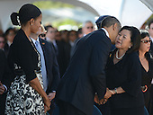 United States President Barack Obama kisses the cheek of Irene Hirano Inouye, wife of the late Senator Daniel Inouye (Democrat of Hawaii), near the casket of the late Senator Inouye at the National Memorial Cemetery of the Pacific during ceremonies on Sunday, December 23, 2012.  Senator Inouye was a Medal of Honor recipient and a United States Senator since 1963.  First lady Michelle Obama looks on from left..Credit: Cory Lum / Pool via CNP
