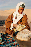 A camel trader prepares food at camp in the Saharah desert in the south of Tunisia