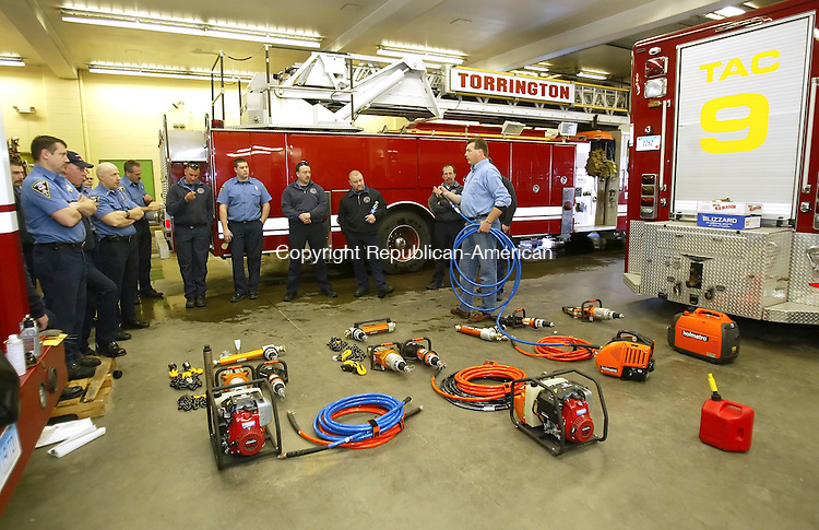 TORRINGTON, CT, 03/21/07- 032107BZ01- Torrington firefighters listen as Mark Laigle, Northeast Regional Manager for Holmatro Rescue Equipment, in blue shirt holding hose, talks about  the department's new equipment Wednesday afternoon.     <br /> Jamison C. Bazinet Republican-American