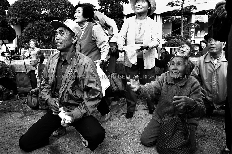 Towa, Japan..Old folk reach out to grab free bags of beans being thrown out during the annual autumn festival...All photographs ©2003 Stuart Isett.All rights reserved.