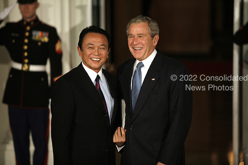 Washington, DC - November 14, 2008 -- United States President George W. Bush greets Taro Aso, Prime Minister of Japan to the White House for a working dinner at the start of the G20 Summit on Financial Markets and the World Economy..Credit: Gary Fabiano - Pool via CNP