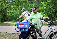 Bill Blair of Bentonville pauses from his ride to enjoy his dog, Thursday, May 21, 2020 at Slaughter Pen bike trail in Bentonville. Blair moved to his home at the Bentonville Square in February where he enjoys a daily ride. Check out nwaonline.com/200522Daily/ for today's photo gallery. <br /> (NWA Democrat-Gazette/Charlie Kaijo)