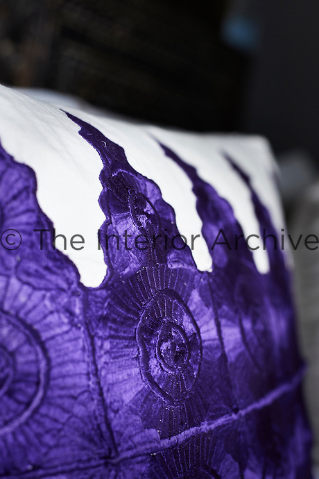 A detail of embroidered purple and white pillow.