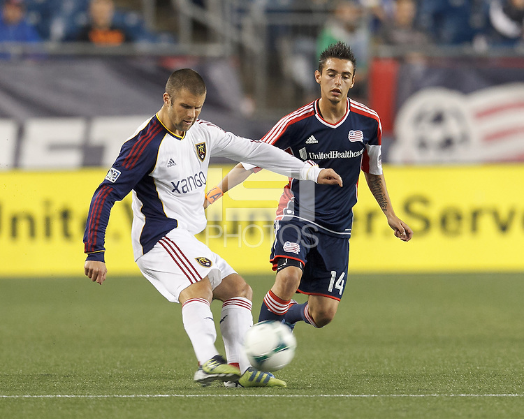 Real Salt Lake defender Chris Wingert (17) crosses the ball as New England Revolution midfielder Diego Fagundez (14) closes. In a Major League Soccer (MLS) match, Real Salt Lake (white)defeated the New England Revolution (blue), 2-1, at Gillette Stadium on May 8, 2013.