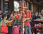 Worshippers light candles in teh entryway of Longshan Temple, Taipei