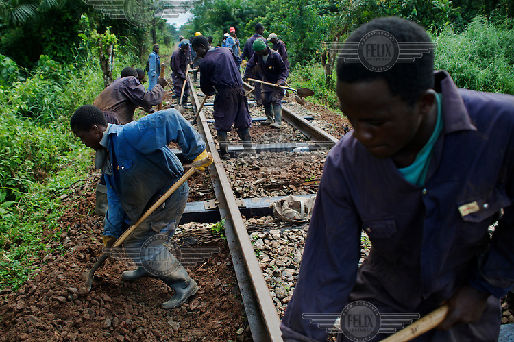Workers constructing a train line linking an iron ore mine, owned and operated by Mittal Steel, and the site of the smelter.
