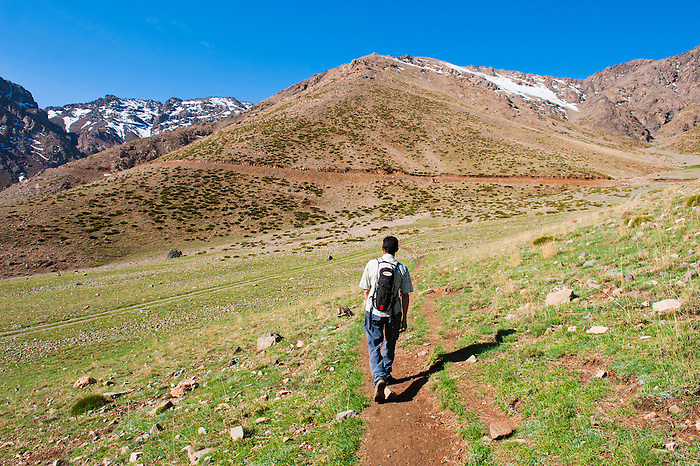 Photo of a trekking tour guide walking at Oukaimeden ski resort in summer, High Atlas Mountains, Morocco, North Africa, Africa. This photo of trekking tour guide was taken at Oukaimeden in the High Atlas Mountains of Morocco. Oukaimeden is the highest point at which you can ski in Africa and is located in the High Atlas Mountains.