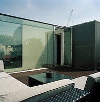 The master bedroom and bathroom are encased in a curving plywood container, sprayed with dark rubber and faced in a mesh of shimmering steel, dubbed The Cloud. The roof terrace has been arranged as a series of outdoor rooms, wrapping around The Cloud, defined by changes in floor surface and planting. The shimmering steel of The Cloud creates a sculptural centrepiece to the garden.