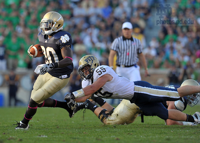 Pittsburgh Panthers linebacker Max Gruder (55) attempts to tackle Notre Dame Fighting Irish running back Cierre Wood (20) in the fourth quarter at Notre Dame Stadium. Notre Dame won 23-17.
