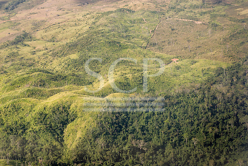 Pará State, Brazil. Aerial view of rain forest with cleared cattle pasture and mountains with rain forest.
