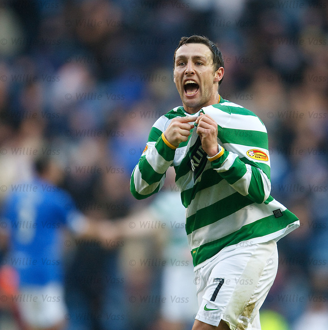 Scott McDonald celebrates to the Celtic fans by pointing to the badge at the final whistle