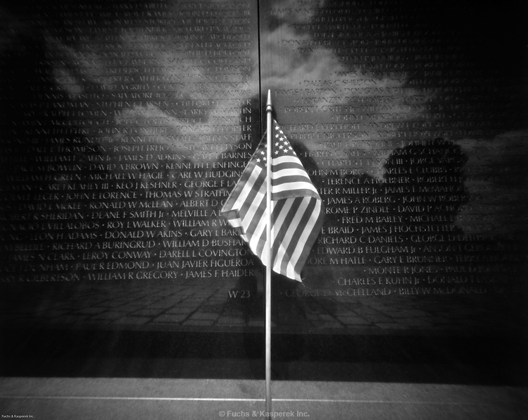 A small solitary American flag rests against to roll of names on the Vietnam Veterans Memorial in Washington, D.C.