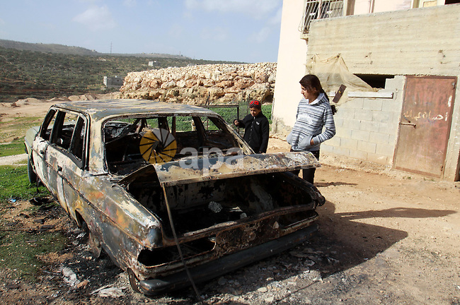 Palestinian children inspect wreckage of a car in the village of Majdal Bani Fadel, near the West Bank City of Nablus, 20 December 2012. According to Palestinian security officials two cars were set on fire in a raid by Jewish settlers.  Photo by Nedal Eshtayah