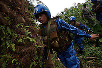 Indian female Peacekeepers from the Indian FPU ( formed police unit ) search in an orchid for hidden drugs while providing armed  support to the liberian national police ( in the background ) during a cordon and search operation in Monrovia, Liberia on Monday March 19 2007. .103 Indian police personnel  were specially selected to take part in the UNMIL peacekeeping mission in Liberia for an initial deployment of 6 months. .They are the first contingent entirely formed by women in the history of the United Nations Peacekeeping..their mission in the country is to provide fire support to the unarmed liberian security forces. In india these women distinguished themselves by operating in the most troubled areas of the country taking part in counter insurgency and crowd control special operations.