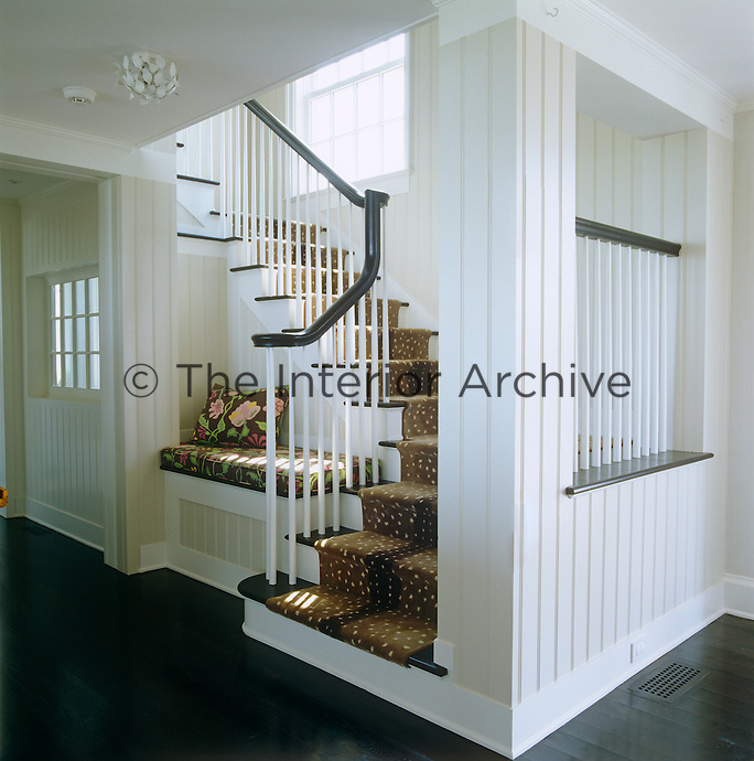 The contemporary staircase leading off the main hall is partly enclosed by a wooden partition wall