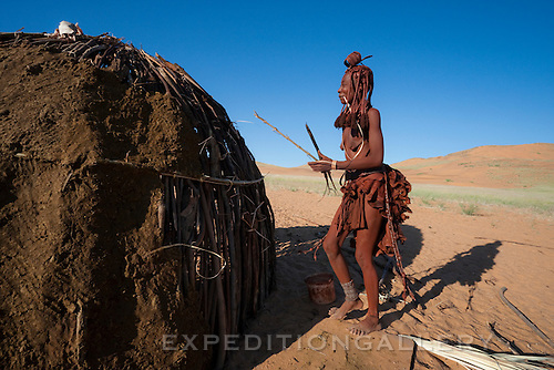 A Himba woman holding sticks and a palm leaf fiber while building a traditional hut made of wood and cow dung. Himba women cover their bodies with a mixture of ochre and butter fat giving their skin and hair a reddish coloration. Himba are nomadic herders of goats and cattle, living in the dry desert regions of northwestern Namibia and southern Angola. [NO MODEL RELEASE]