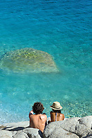 A young couple relax on rocks overlooking the clear azure waters of the Mediterranean