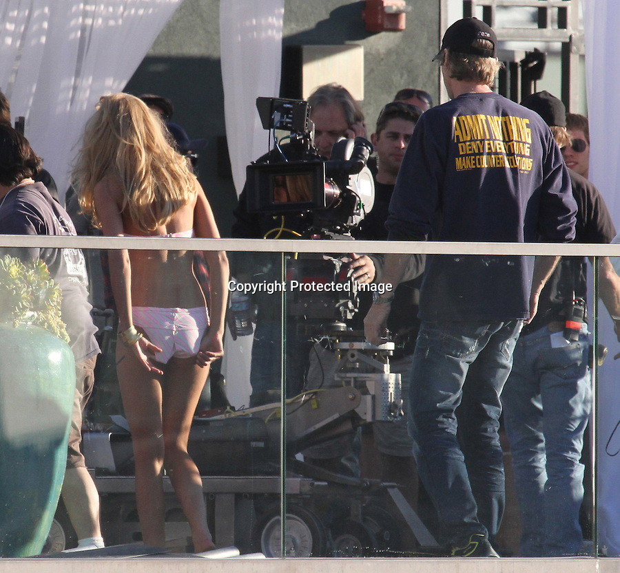 "Exclusive February 11th 2011   Saturday ..Victoria's Secret commercial directed by Michael Bay for a new summer line of clothing called the ""Bombshell"" edition. .Filming on the penthouse pool of the Eastern building  in downtown Los Angeles ..The girls sitting by the pool in order from left to right Alessandra Ambrosio Erin Heatherton Adriana Lima Chanel Iman & Candice Swanepoel ..Erin was showing off her butt doing a solo walk across the pool .Alessandra Ambrosio text messaged on her phone while watching the other two girls film there scene .Candice was sporting her long legs in a lime green bikini .Erin & Lily did a sexy scene holding each other & laughing it up with director Michael .Bay..The girls were wearing a pink & black Polka Dot bikini & hot pink lace bra & panties  .They brought in a male model for one of Alessandra Ambrosio's scene as she shook her long legs wearing Gold high heel shoes & butt floss..Allessandra was getting sunscreen rubbed into her breast and cleavage area wearing a hot pink bikini  ..Erin  was wearing a harness so she would hang off the roof but they ended up cutting the scene. ....AbilityFilms@yahoo.com.805-427-3519.www.AbilityFilms.com"