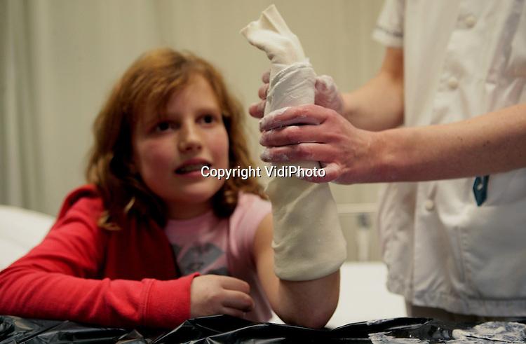 Foto: VidiPhoto..AMERSFOORT - In het Meander Medisch Centrum, locatie Lichtenberg, in Amersfoort wordt de 11-jarige Loes Masteling uit Hoogland vrijdag geholpen aan een gebroken pols. Het meisje liep de botbreuk op bij het schaatsen. Nederlandse ziekenhuizen draaien overuren door ongevallen op het ijs en de gladheid. Vergeleken met een normale winterweek worden er minstens 80 procent meer botbreuken behandeld. Dit weekend verwachten de ziekenhuizen een record aan ongevallen.