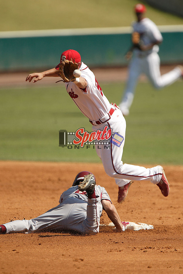 North Carolina State shortstop Jonathan Diaz (23) goes up high for a throw as Florida State's Shane Robinson slides in with a double at the 2006 ACC Baseball Championship at the Baseball Grounds of Jacksonville in Jacksonville, FL, Saturday, May 27, 2006.  Florida State defeated North Carolina State 7-3.