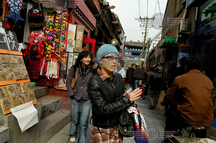 A young woman wearing glasses and a leather jacket shops in a market near Hou Hai lake.