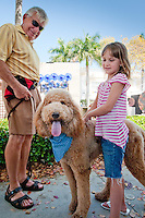 Six-year-old Emily Bird, Michigan, poses with Dasher, a Standard Poodle, and his best friend, Al Staley, Naples, during the 23rd Annual Downtown Naples Festival of the Arts, hosted by The von Liebig Art Association and Downtown Association, Naples, Florida, USA, March 26, 2011. Photo by Debi Pittman Wilkey