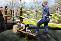 Olivia Hill, 8, attempts to keep her balance on a spring board Tuesday, March 24, 2020, as her aunt Amber Hill attempts to rock her off at Wilson Park in Fayetteville. The city is shutting down all playgrounds, sports parks, restrooms, basketball courts and water fountains as a means to prevent the spread of covid-19. Visit nwaonline.com/200325Daily/ and nwadg.com/photos for a photo gallery.<br /> (NWA Democrat-Gazette/David Gottschalk)