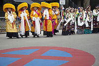 Switzerland. Basel. St. Jakobshalle. A group of tibetan men and women dressed in traditional clothings wait for the arrival of His Holiness the Dalai Lama. They hold in their hands white scarfs, called khata. In most cases the giver will receive his or her Khata back from the given, as a token of blessing back to them. When a Khata is offered to His Holiness the Dalai Lama and received back, it will be cherished and preciously kept as it is now a very special blessing, a talisman and protector. Stop and parking prohibited road sign painted on the concrete road. 7.02.2015 © 2015 Didier Ruef