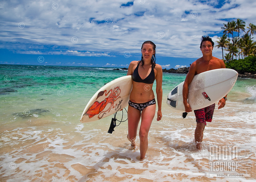 Young couple walking down Laniakea Beach after a surfing session