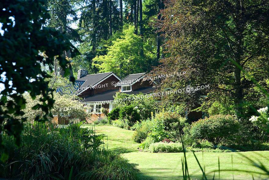 A wood-shingled waterfront weekend vacation retreat, featuring this raised dormer, sits amid towering evergreen trees and wonderful gardens on the edge of Washington State's Vashon Island.