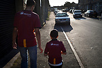 A man and boy heading away from the ground after Bradford City played Carlisle United in a Skybet League 2 fixture at Valley Parade. The home team were looking to bounce back after being relegated during a disastrous 2018-19 season on and off the pitch. Bradford won the match 3-1, watched by a crowd of 14, 217.