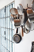 A jumble of cooking pots and frying pans hang from hooks in the kitchen.