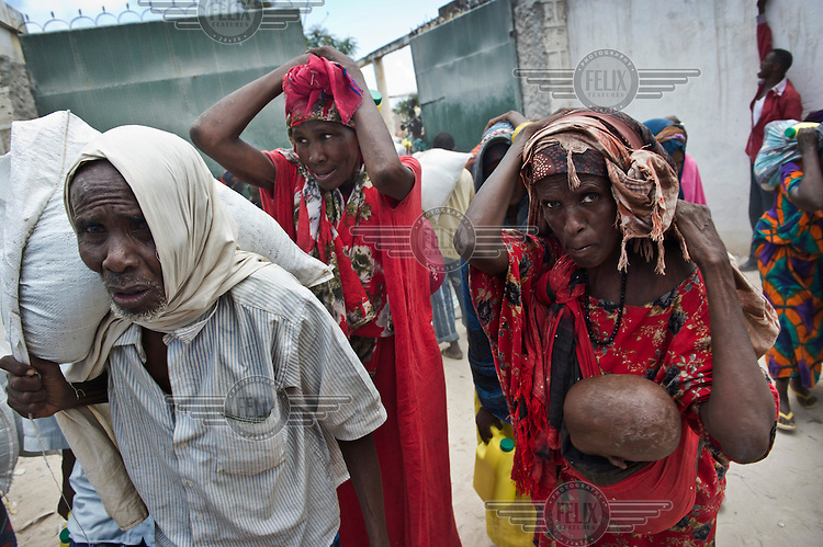 People walk along a Mogadishu street holding their hands above their heads to protect themselves from raoming militias. Although Al Shabab have been driven out of the city, security is still a problem.
