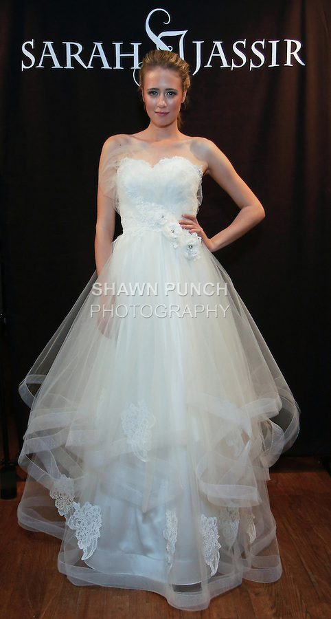 "Model poses in an Angelique Bridal dress - tulle and lace ball gown with tiered skirt, by Sarah Jassir, for the Sarah Jassir Spring 2013 ""La Reve: The Dream"" collection, during Bridal Fashion Week New York."