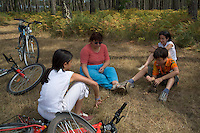 Family sitting in the grass in Landes Forest, Aquitaine, France.