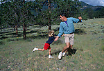 A father and his daughter play tag in a meadow in Rocky Mtn Nat'l Park, CO