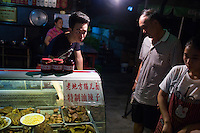 Workers serve small plates of snacks to people eating at Lao Di Feng Mao Er Mien near Ciqikou ancient town in the Shapingba district of Chongqing, China. These snacks are usually eaten while drinking beer. The restaurant is primarily outdoors and is open 24 hours a day. The restaurant has been for about 10 years. At night, the restaurant serves mostly neighborhood locals. <br /> <br /> Ciqikou's ancient town is a major tourist destination in Chongqing, but at night, the tourists disappear and locals come out to eat from street food vendors in the area.