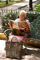 Elderly Mexican woman sitting on a park bench and reading a newspaper in the Zocalo, Cholula, Puebla, Mexico.