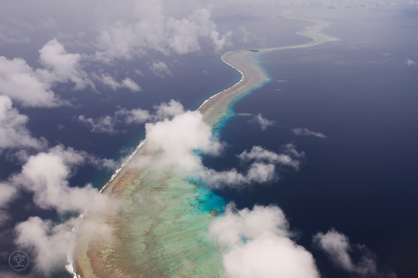 The fragile line of the coral reef that forms an atoll snakes into the distant blue waters of the Pacific Ocean.