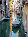 A quiet, dark and narrow canal with boats, Venice, Italy.