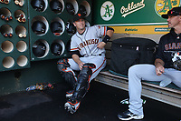 OAKLAND, CA - JULY 21:  Buster Posey #28 of the San Francisco Giants gets ready in the dugout before the game against the Oakland Athletics at the Oakland Coliseum on Saturday, July 21, 2018 in Oakland, California. (Photo by Brad Mangin)