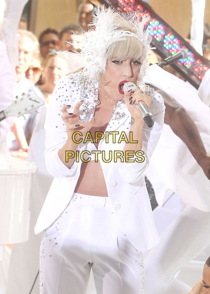 "LADY GAGA (Stefani Joanne Angelina Germanotta) .performs live on NBC's ""TODAY"" Show at Rockefeller Center, New York, NY, USA, 9th July 2010..on stage music concert gig half length white microphone singing suit jacket bra feather lace ear muffs head band hair hairband silver beaded studded embellished hand .CAP/ADM/AC.©Alex Cole/AdMedia/Capital Pictures."