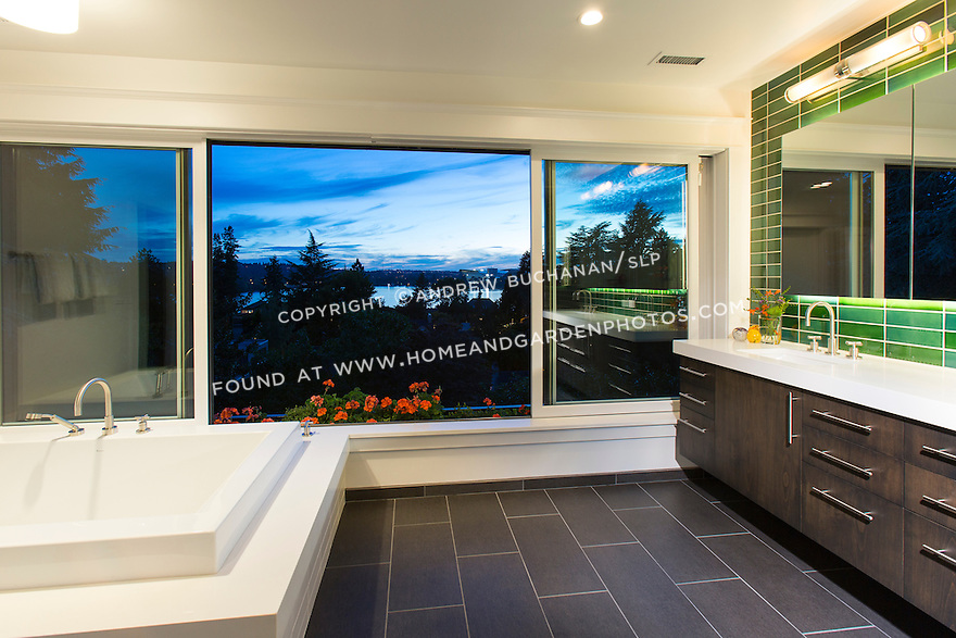 Floor-to-ceiling sliding windows offer a view out over the water from the master bathroom. This image is available through an alternate architectural stock image agency, Collinstock located here: http://www.collinstock.com