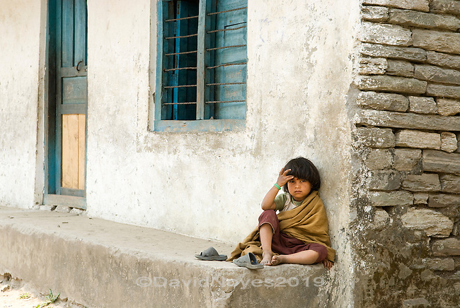 A young boy sits outside the door of his school in the village of Ghandruk in the Annapurna region of Nepal. Since the ceasefire of 2006, Nepal has given birth to a new generation facing new challenges, but now with open doors inviting people from around the world to walk the stone steps of their mountain villages.