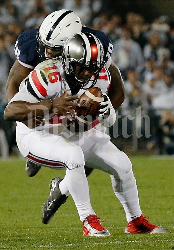 Ohio State Buckeyes quarterback J.T. Barrett (16) is sacked by Deion Barnes (18) in the second quarter of their game at Beaver Stadium in State College, PA on October 25, 2014. (Columbus Dispatch photo by Brooke LaValley)